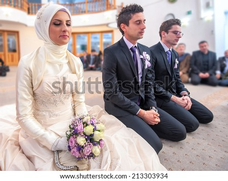 Bride and groom sitting in mosque at a wedding ceremony - stock photo
