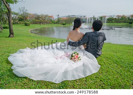 Bride and groom sitting near the lake - stock photo