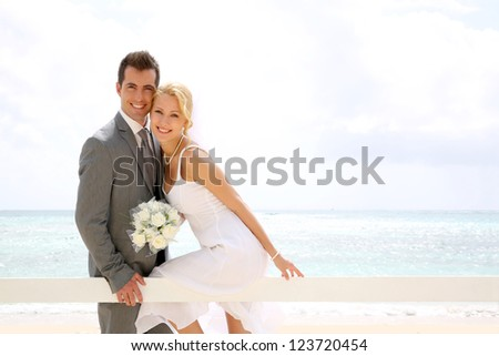 Bride and groom sitting on a fence by the beach - stock photo