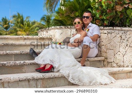 Bride and groom sitting on the steps. - stock photo