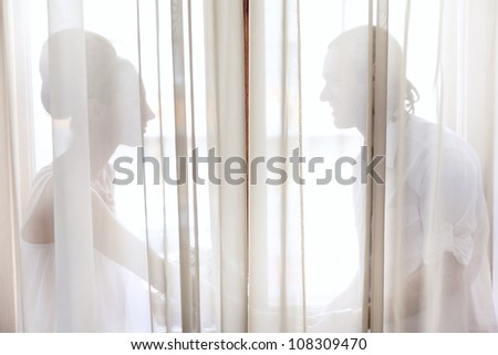 Bride and groom sitting on windowsill behind the white curtain