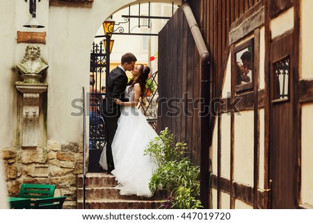 Bride and groom stand in a stone arch which leads to the street