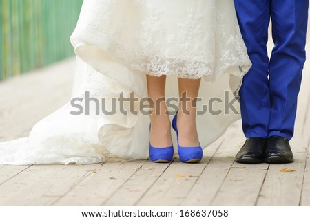 bride and groom standing on bridge in park - stock photo