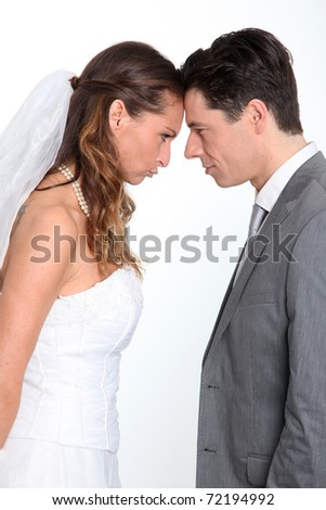 Bride and groom standing on white background with upset look
