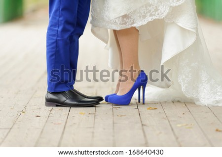 bride and groom standing on wooden bridge in park - stock photo