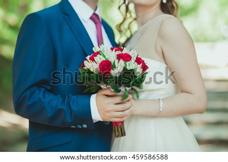 Bride and groom standing side by side in the arms of the bride holding a beautiful bouquet, wedding
