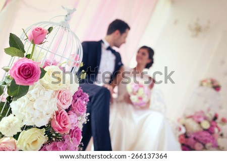 Bride and groom surrounded by flowers - stock photo