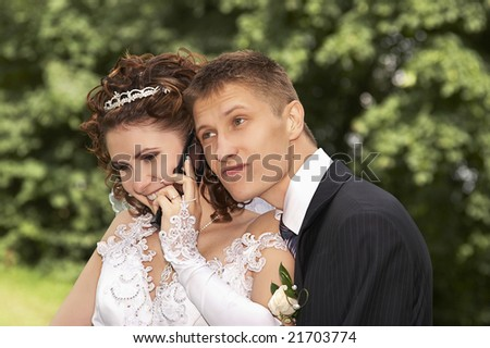Bride and groom talking by phone