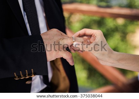 Bride and groom, the groom dress the ring for the bride, male and female hand with wedding rings, wedding ceremony, together forever, time, happiness
