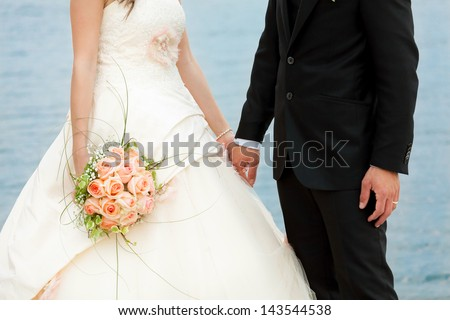 bride and groom they walk to the lake - stock photo