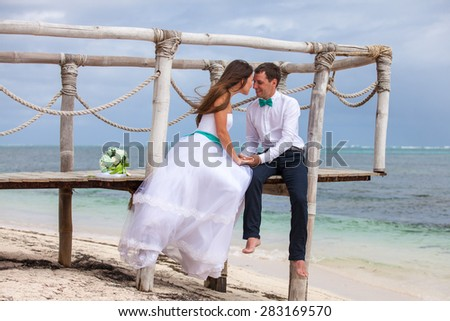 Bride and groom together on a wharf. - stock photo