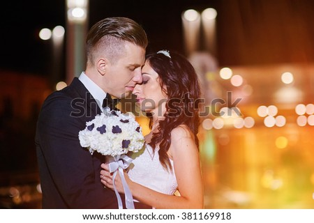 bride and groom walk in city at night