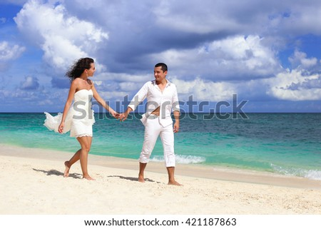Bride and groom walking and holding hands, romantic vacation at tropical beach