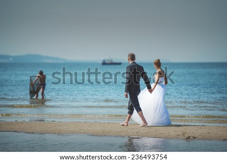 Bride and groom walking at the coast of Baltic Sea