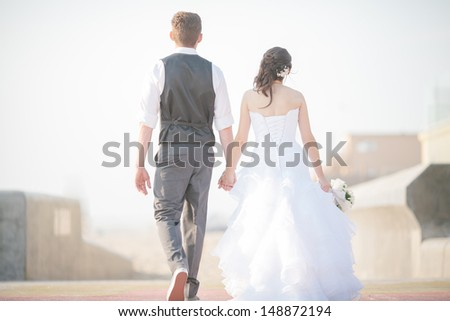 Bride and Groom Walking Away - stock photo