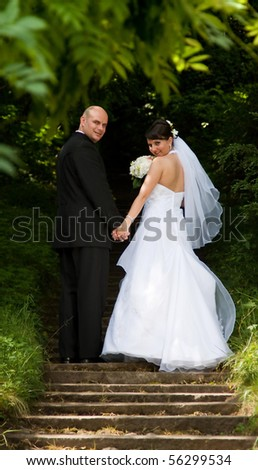 Bride and groom walking in park - stock photo