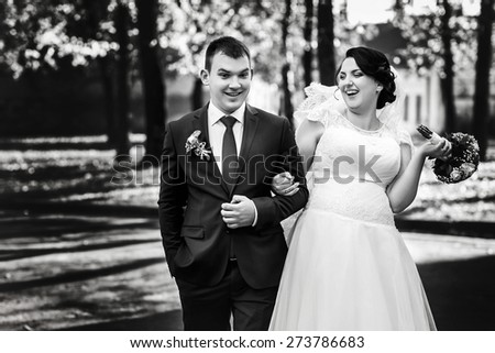 bride and groom walking  near trees in autumn park
