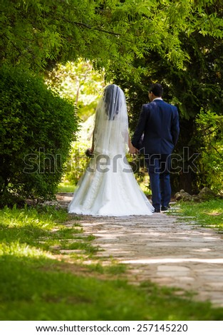 Bride and groom walking on a park in wedding day - stock photo