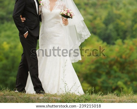 bride and groom walking on green grass