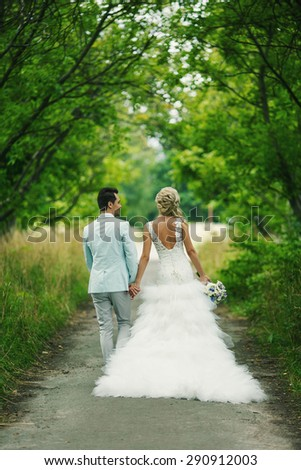 Bride and groom walking on the alley between trees