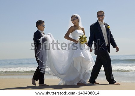 Bride and Groom with brother walking on beach - stock photo