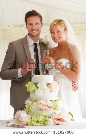 Bride And Groom With Cake Drinking Champagne At Reception - stock photo