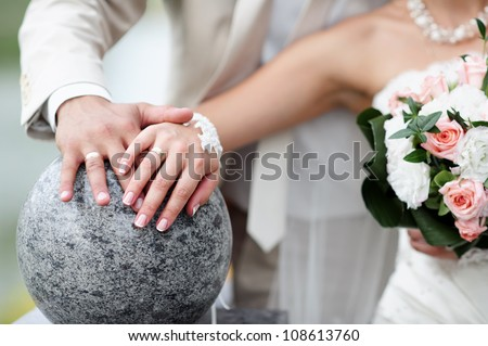 Bride and groom with flowers and wedding rings - stock photo