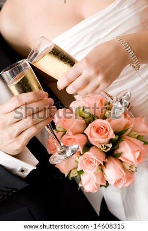 bride and groom with glasses of champagne and red rose bouquet - stock photo