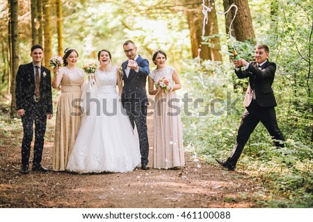 bride and groom with happy groomsmen and bridesmaids having fun and popping champagne, hilarious moment. Funny guys