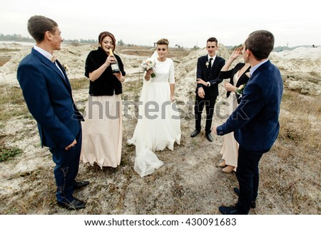 bride and groom with happy groomsmen and bridesmaids having fun and toasting with champagne, luxury wedding celebration, hilarious moment