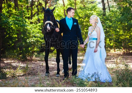 Bride and groom with horse. Portrait of a fashion bride and groom with brown horse.