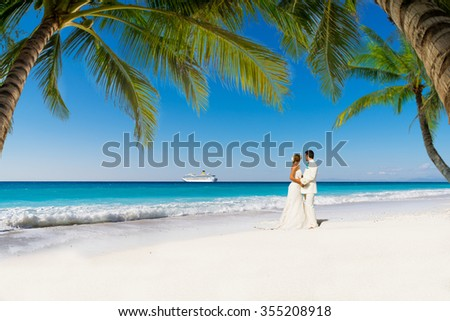bride and groom with palm trees on a tropical beach - stock photo