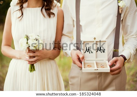 bride and groom with rings and bouquet - stock photo