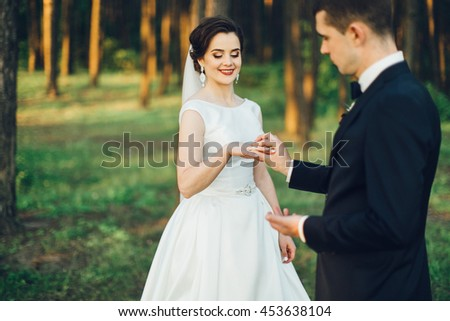 Bride and groom with wedding rings in the wood - stock photo