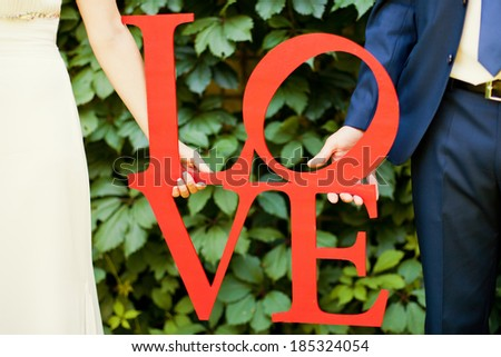 bride and groom with wooden word - stock photo