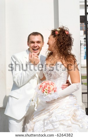 bride and groom - young couple in wedding wear with bouquet of roses.