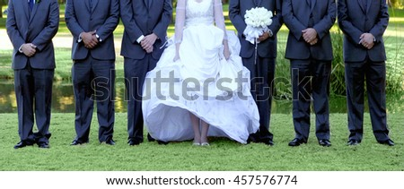 Bride and Groomsmen Lined up Outdoors on Green Grass - stock photo
