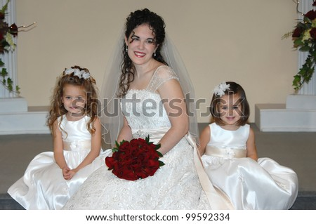 Bride and her two flower girls rest on the church steps on her wedding day.  Bride has on gown with cap sleeves and little girls have on sleeveless dresses with white flowers in their hair. - stock photo