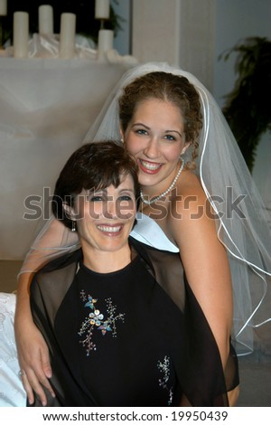 Bride and mom sit side by side in church sanctuary.  Both are smiling and happy.  Mom is in black. - stock photo