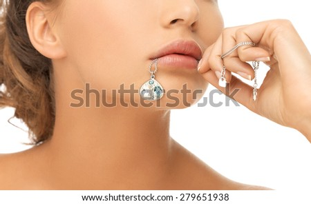 bride and wedding concept - beautiful woman holding shiny diamond pendant in mouth - stock photo