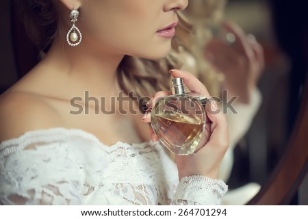 bride applying perfume  - stock photo