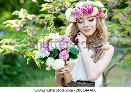Bride. Beautiful young blond woman in the park with flower wreath and bouquet on a warm summer day.  - stock photo
