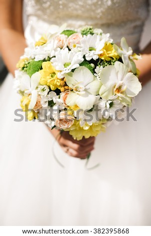 Bride bouquet with white roses, orchids, daisies