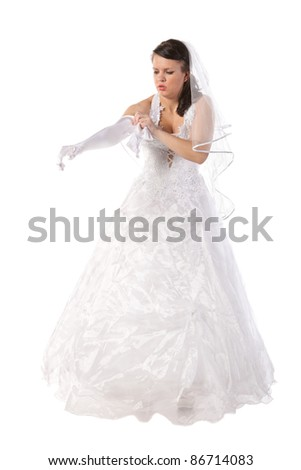 bride dressed in elegance white wedding dress gets into long gloves, isolated on white - stock photo
