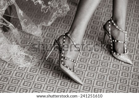 Bride dresses shoes before the wedding ceremony  - stock photo