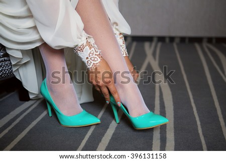 Bride dresses shoes before the wedding ceremony. Bride attributes. Morning of the bride. Preparations for the wedding ceremony - stock photo