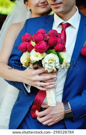 Bride embraces bridegroom from the back and holding a bouquet of flowers piany and tea rose . groom's suit of blue color. Warm , raostnye hug a loved one. - stock photo