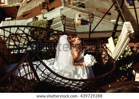 Bride enjoys summer sun standing on the spiral stairs on the roof - stock photo