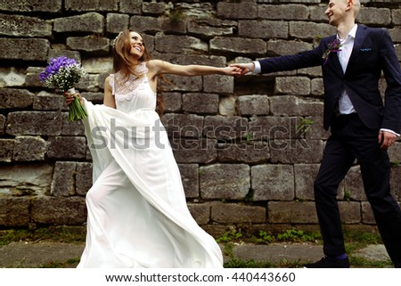 Bride entails a groom walking along a big stone wall