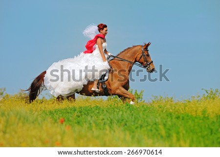 Bride galloping on sorrel horse in field.